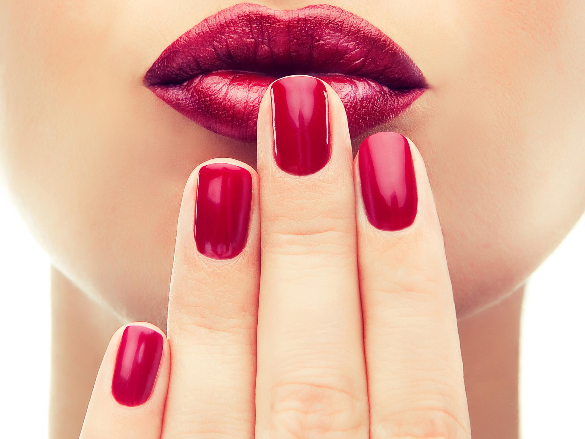 Des ongles avec du vernis rouge posés sur une bouche rouge