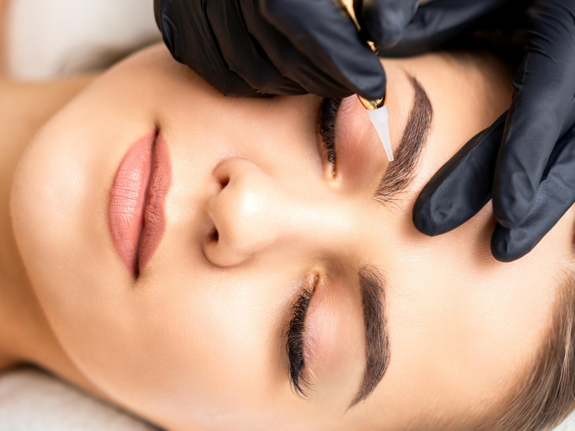 Une jeune femme se faisant tatouer les sourcils dans le cadre des formations en maquillage permanent dispensées par Ambre Select.
